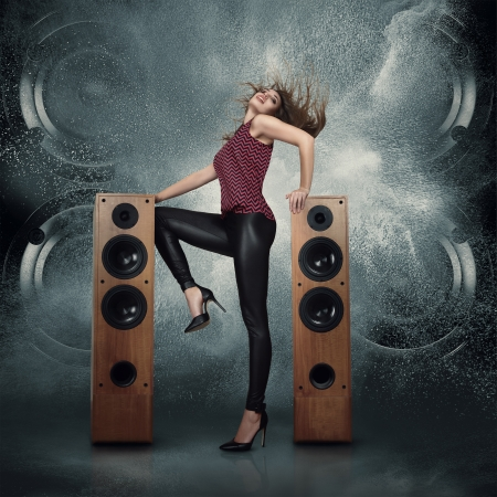 Photo for Abstract concept of powerful audio speakers blast out a cloud of dust against dark background and dancing woman posing in front of them - Royalty Free Image
