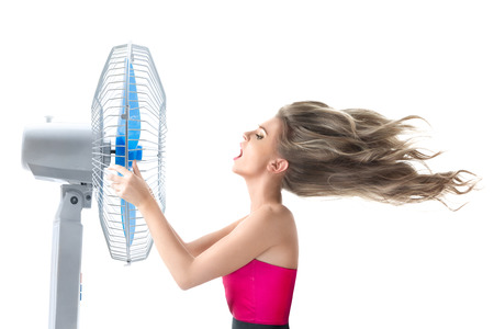 Photo for Young woman cooling face under wind of cooler fan isolated on white background - Royalty Free Image
