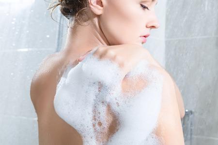 Photo pour Young woman washing body in a shower. Rear view - image libre de droit
