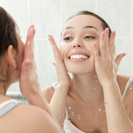 Photo pour Young woman washing her face with clean water in bathroom - image libre de droit