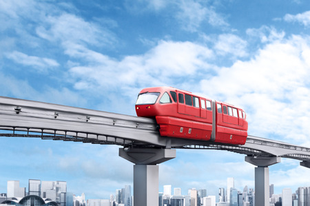 Foto per Red monorail train against blue sky and modern city in background - Immagine Royalty Free