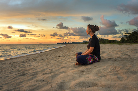Foto de Woman sitting on beach sand and relaxing at sunset time - Imagen libre de derechos