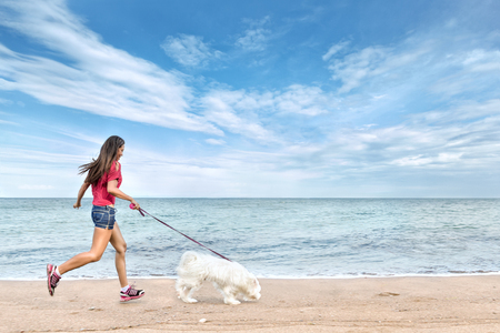 Photo for Young beautiful asian woman walking with dog near sea - Royalty Free Image