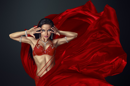 Photo for Beautiful belly dancer perfoming exotic dance in red flutter dress - Royalty Free Image