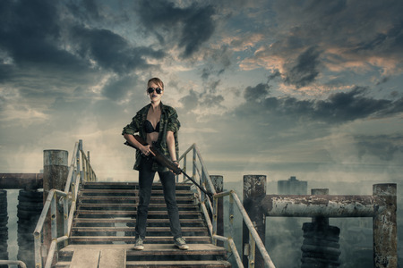 Photo pour Apocalyptic portrait of young sexy woman warrior against of ruined abandoned city - image libre de droit