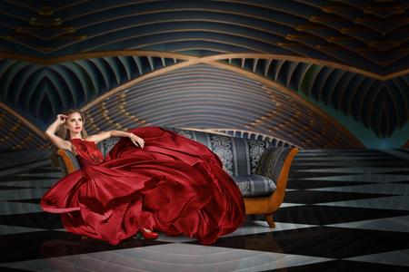 Photo pour Fashion portrait of beautiful woman in long dress sitting on sofa - image libre de droit
