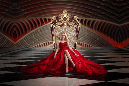 Foto de A woman in a luxurious gown dress sitting on a queen's throne - Imagen libre de derechos