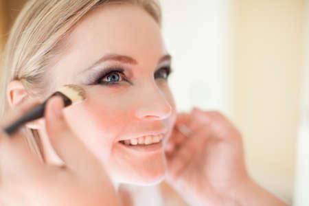 Young beautiful bride having wedding make-up by make-up artist