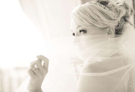 Foto de Gorgeous smiling blonde bride  in front of a Penthouse window at a modern hotel peaking over her veil - Imagen libre de derechos