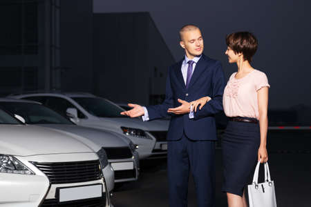 Young couple collecting new car at dealership lot