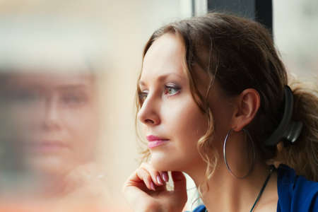 Photo for Sad young woman looking through window - Royalty Free Image