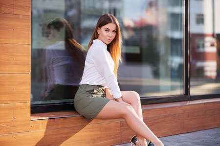Photo for Young fashion woman sitting on the mall window in a city street. Stylish female model in white blouse and short skirt outdoor - Royalty Free Image