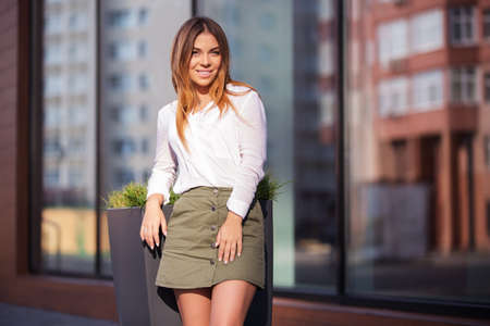 Photo for Young fashion woman standing next to mall window in a city street. Stylish female model in white blouse and short skirt outdoor - Royalty Free Image