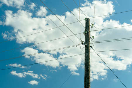 Foto de old wooden power post column entangled with live wires against the blue sky with clouds - Imagen libre de derechos