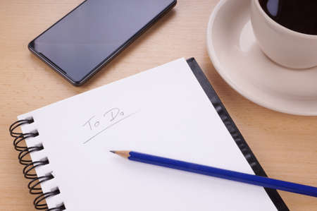Foto de to-do list with note pad, pencil, mobile phone and cup of coffee on desk - Imagen libre de derechos