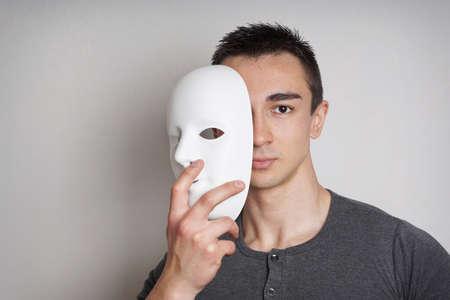 Photo pour young man taking off plain white mask revealing face - image libre de droit