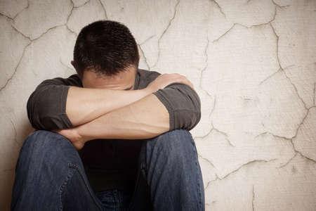 Foto de depression devastated young man hiding his face - Imagen libre de derechos