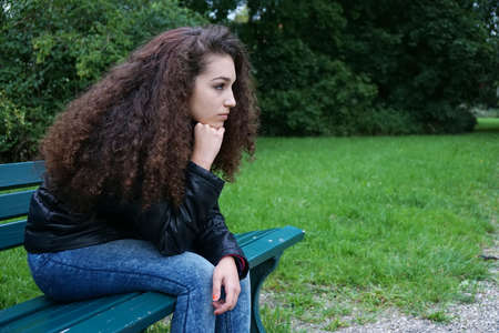 sad female teenager sitting on park bench