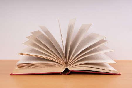 Foto de open hardcover book with turning pages in fan shape on desk - Imagen libre de derechos