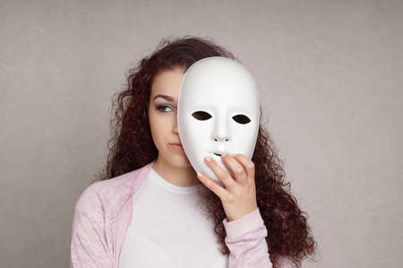 Photo for sad young woman hiding her face behind mask, identity or personality concept - Royalty Free Image