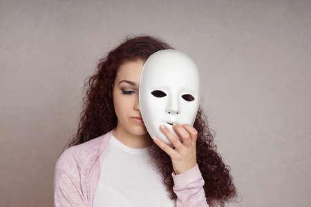 Photo pour sad depressed young woman hiding her face behind mask - image libre de droit
