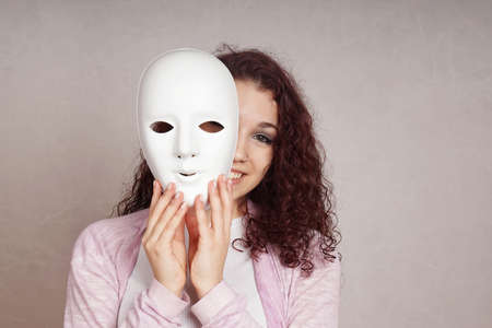 Photo pour smiling young woman peeking from behind mask - image libre de droit