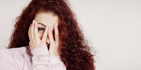 embarrassed young woman covering face with hands and peeking through her fingers