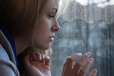 Photo for sad young woman looking through window on rainy day. depression concept. - Royalty Free Image