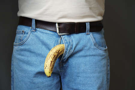 Foto de old limp drooping banana hanging from genital area of clothed unrecognizable man, impotence erectile dysfunction or limp-dick concept - Imagen libre de derechos
