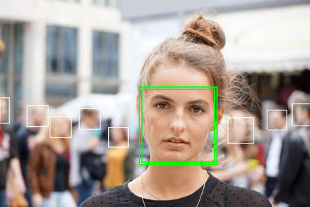 Photo for young woman picked out by face detection or facial recognition software - several other faces detected in crowd of people in background - Royalty Free Image
