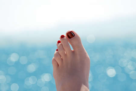 Female foot over blue ocean on sunny summer day