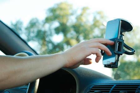 Foto de Male hand and smartphone in a car - Imagen libre de derechos