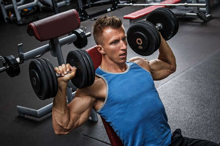Photo pour Muscular man training his shoulders with dumbbells - image libre de droit