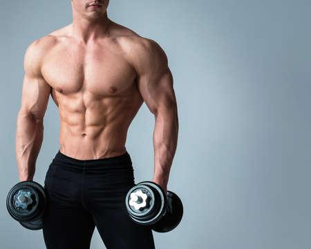 Foto de Young bodybuilder with dumbbells in studio - Imagen libre de derechos