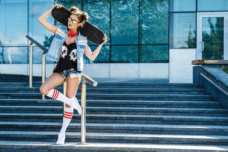Foto de Stylish girl with a skateboard on the street - Imagen libre de derechos