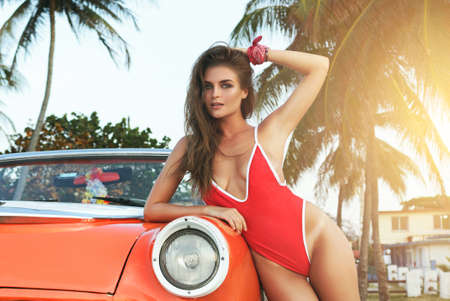 Photo pour Sexy woman in red swimsuit and retro cabriolet car on the beach - image libre de droit
