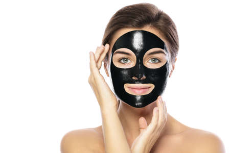 Photo for Woman with purifying black mask on her face isolated on white background - Royalty Free Image