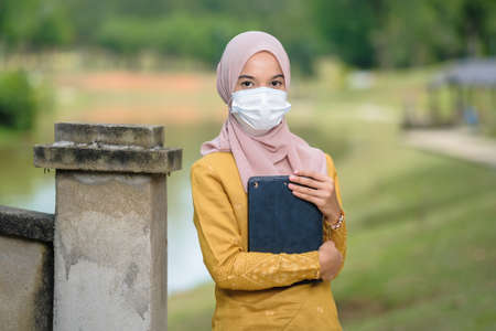 Asian muslim student woman with traditional dress wearing medical face mask at le lake.