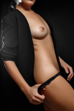 Foto de naked Breasts and body of young woman in black jacket and black panties on black background - Imagen libre de derechos