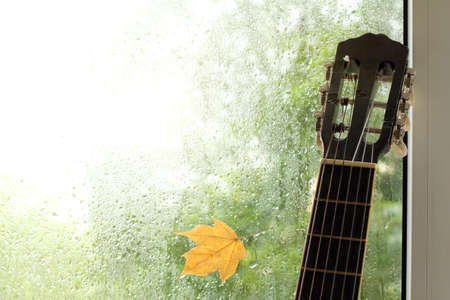 acoustic guitar leaning against the wet window with adhered maple leaf/ Autumn musical mood