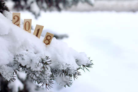 Foto de snow-covered Christmas tree decorated with wooden numeric  that indicate the coming of the new year \ winter atmosphere 2018 - Imagen libre de derechos