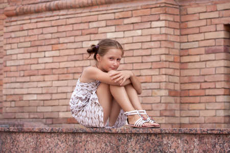 Photo pour little smiling girl lying on a stairs of urban building. - image libre de droit