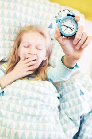 Foto de alarm clock disturbing a sleeping little girl that is defocused - Imagen libre de derechos