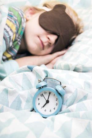 Foto de alarm clock disturbing a sleeping little girl that is defocused. daily regime  - Imagen libre de derechos