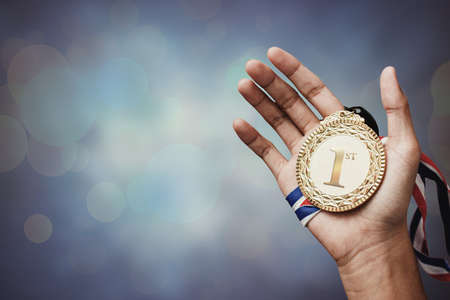 Photo for hand holding up a gold medal as a winner in a competition - Royalty Free Image