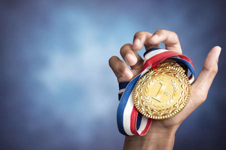 Photo pour hand holding up a gold medal as a winner in a competition - image libre de droit