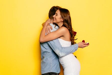 Photo pour Happy woman hugging her boyfriend after getting marriage proposal on St. Valentine's day. - image libre de droit