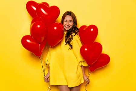 Photo for Happy Valentine's day. Smiling girl holding red air balloons in two hands, posing at camera. Dressed in yellow warm dress. - Royalty Free Image