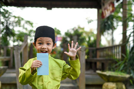Photo pour A Malay boy in Malay traditional cloth showing his happy reaction after received money pocket during Eid Fitri or Hari Raya celebration. - image libre de droit