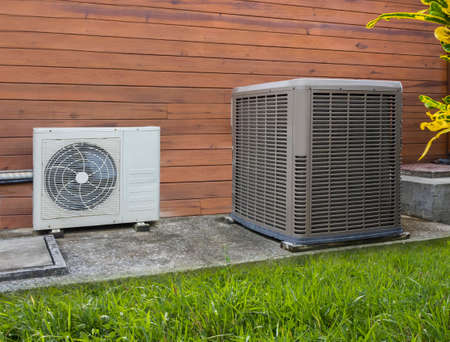 Photo for Two different sized air conditioning heat pumps on the side of a house - Royalty Free Image